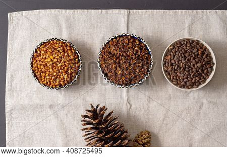 Three Round Bowls With Siberian Pine Nuts. Peeled Nut Kernels, Their Shells, Whole Cone Grains. Near