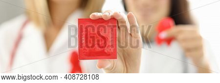 Two Female Doctors Are Holding A Condom And A Red Ribbon. Sexually Transmitted Diseases Concept