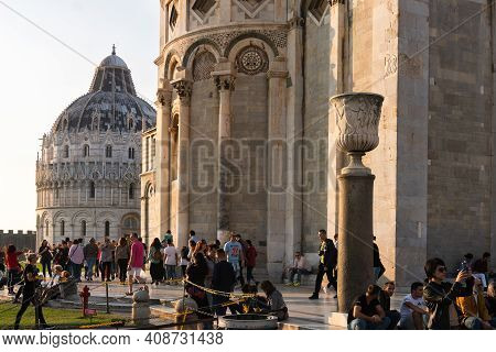 Pisa, Italy-october 21, 2018:tourists Stroll And Admire Piazza Dei Miracoli In Pisa At Sunset