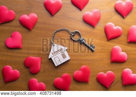 House Key With Home Keyring Decorated With Mini Heart On Rusty Wood Background, Copy Space