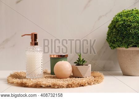 Soap Dispenser, Plants And Burning Candle On Countertop In Bathroom