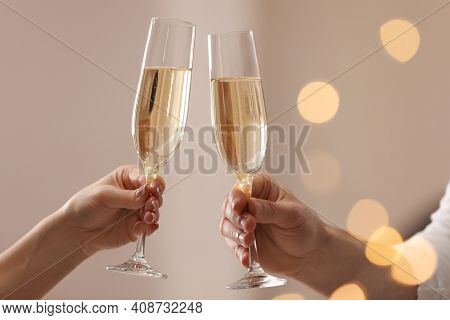 People Clinking Glasses Of Champagne Against Blurred Background, Closeup. Bokeh Effect