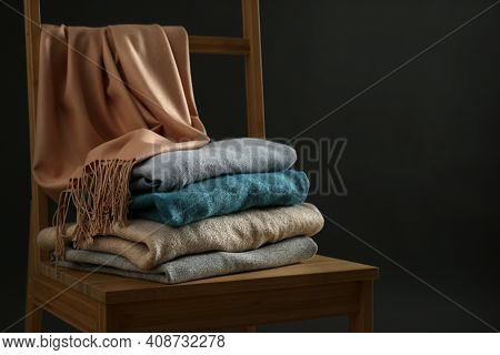 Stack Of Cashmere Clothes On Wooden Chair