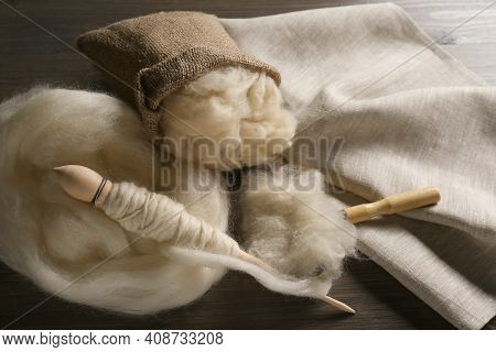 Soft White Wool, Spindle And Comb On Wooden Table