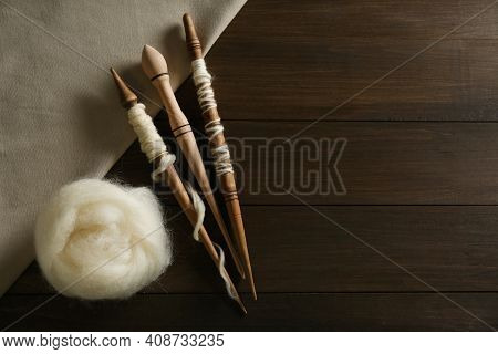 Soft White Wool With Spindles On Wooden Table, Flat Lay. Space For Text
