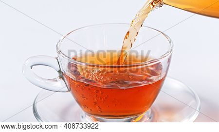 pouring tea to a teacup, close-up