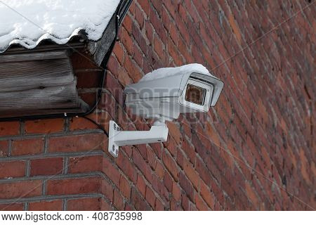 White Cctv Camera On A Red Brick Wall