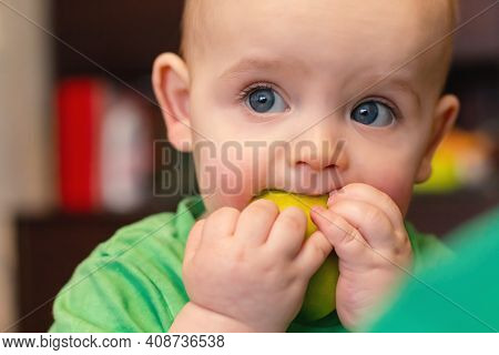 Caucasian Baby Boy Face With Apple. Close Up. First Baby Food. Child Getting Face Dirty While Eating