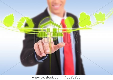 business man pushing a green house eco button