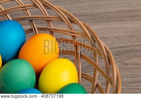 Colorful Easter Eggs In A Wicker Wooden Basket.