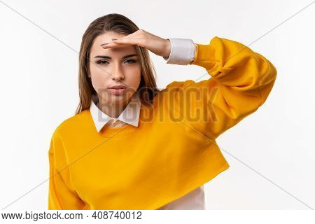 Portrait Of A Curious Brunette Girl In Casual Clothes Looking Far Away With Hand At Her Forehead, Tr