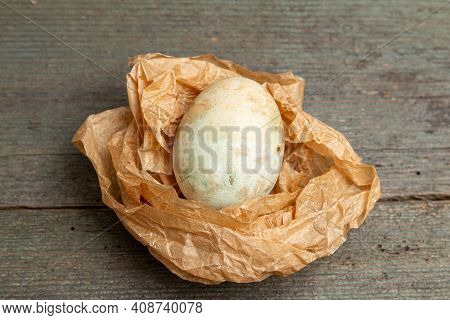 Easter Eggs On Crumpled Paper On A Wooden Table