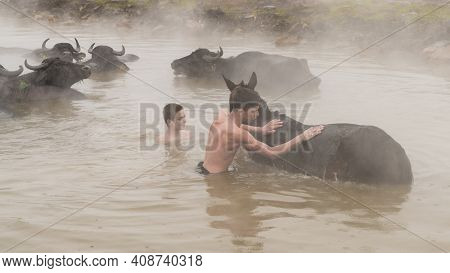 Guroymak, Bitlis, Turkey - February 2020: Boys Washing Their Horse. Animals And Boys In Thermal Wate