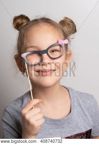 Cheerful Crazy Little Girl Looks Through Rickety Paper Glasses. Festive Costume For A Masquerade. At