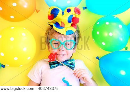 Funny Smiling Child Clown With Multicolored Balloons. April Fools Day Celebration Concept. Birthday