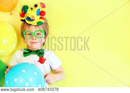 Funny Smiling Child Clown On Yellow Background With Multicolored Balloons, Copy Space. April Fools D
