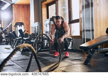 Muscular Young Male Using Crossfit Ropes Indoors
