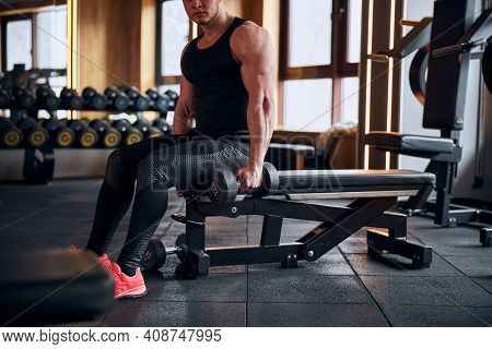 Muscular Athlete Lifting Weights On Bench In Gym