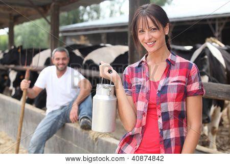 Mujer con una mantequera de leche frente a un rebaño de vacas