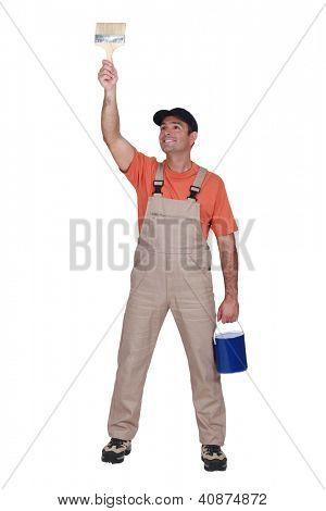 Happy tradesman painting a wall