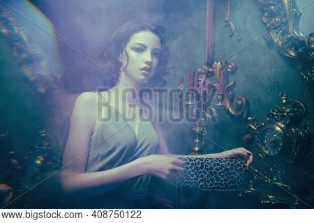 Attractive brunette girl poses in vintage smoky room. Beauty, fashion.
