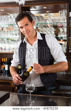 Barman standing behind the bar In restaurant opening a wine bottle