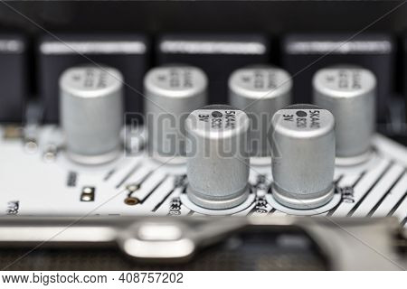A Macro Shot Of Six Capacitors In A Metal Housing, Soldered To The Motherboard Of A Desktop Computer