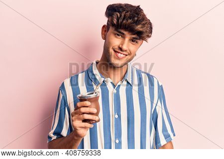 Young hispanic man drinking mate infusion looking positive and happy standing and smiling with a confident smile showing teeth