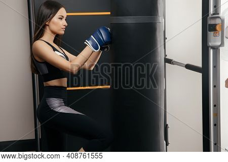A Beautiful 30-year-old Woman Hits A Punching Bag In The Gym During A Workout. The Concept Of Self-d