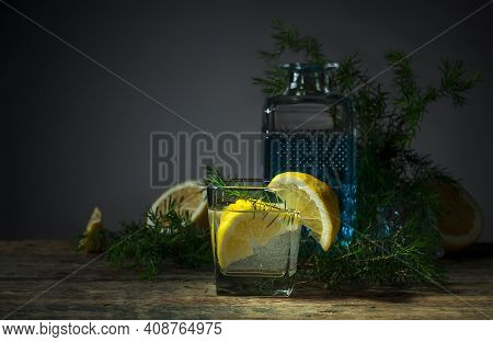 Cocktail With Blue Gin , Tonic And Lemon. Alcoholic Drink With Lemon Slices And Juniper Branch On A