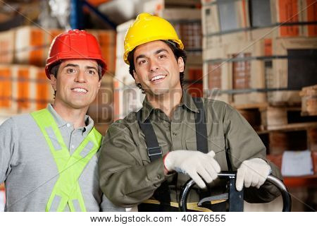 Portrait of two happy foremen wearing hardhats at warehouse