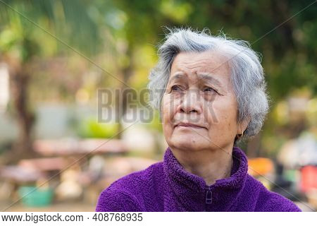 Portrait Of Elderly Asian Woman With Short Gray Hair And Standing Smiling And Looking Up While Stand