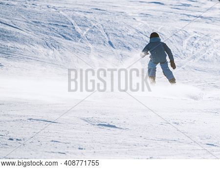 Child Skiing Down A Steep Alpine Piste With Snow Spraying Up Behind Him. Shallow Depth Of Field.