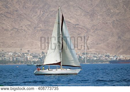 Eilat, Israel - May 13, 2011: The Yacht Sails Along The Lost In The Haze Jordanian Coast Of The Red