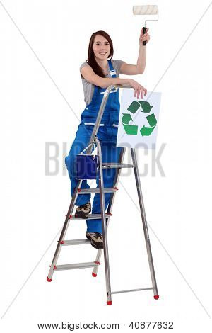 Tradeswoman holding a paint roller and a poster