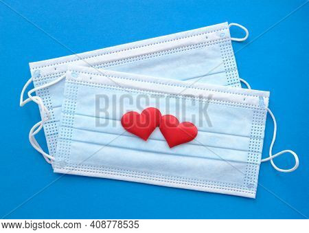 Disposable Face Masks And Two Hearts On Blue Background . Protection, Care And Mutual Assistance Con