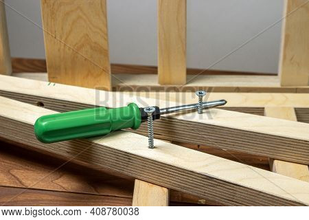Woodwork. Wooden Slats And Working Tools. Metal Screw And Screwdriver. Self-tapping Screw Screwed In