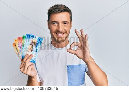 Handsome caucasian man holding swiss franc banknotes doing ok sign with fingers, smiling friendly gesturing excellent symbol
