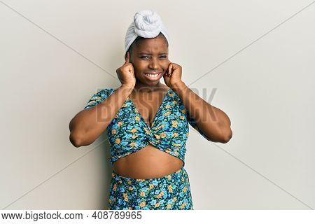 Young african woman wearing hair turban and african style covering ears with fingers with annoyed expression for the noise of loud music. deaf concept.