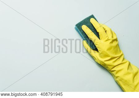 Yellow Rubber Glove Is Holding Sponge On The White Background. Yellow Rubber Glove Is Cleaning With