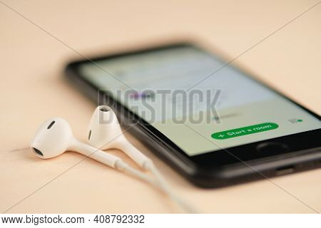 Minsk, Belarus - February 18, 2021: Smartphone on the wooden table with open Clubhouse drop in audio chat app and set of headphones nearby. Shallow depth of field. Focus at start a room button