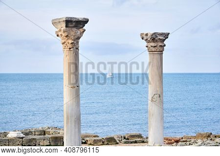 Two Antique Columns In Ruins Against The Background Of The Sea, In Which A Blurred Sailboat Is Visib
