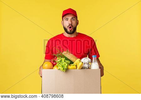 Online Delivery, Shopping And Food Order Concept. Impressed Bearded Courier In Red Uniform Cap, T-sh