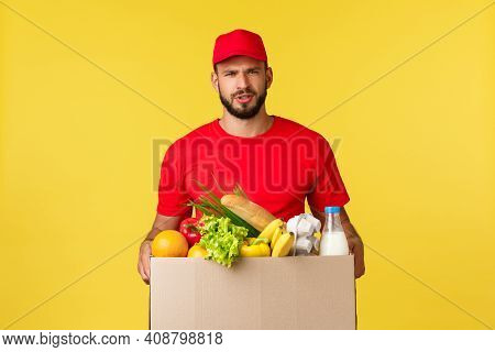 Online Delivery, Shopping And Food Order Concept. Doubtful And Upset Courier In Red Uniform Cap And