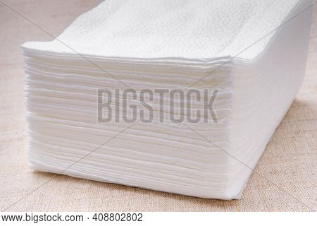 A Stack Of White Paper Napkins On A Light-colored Tablecloth.