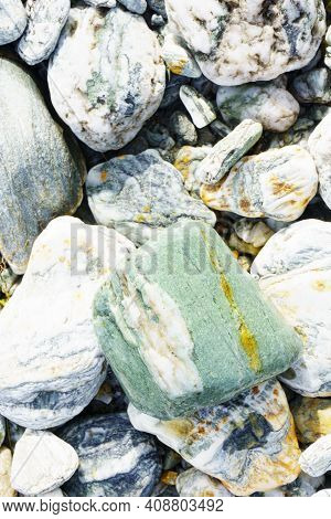 Colored River Stones Of Various Sizes Selective Focus On Greenstone.