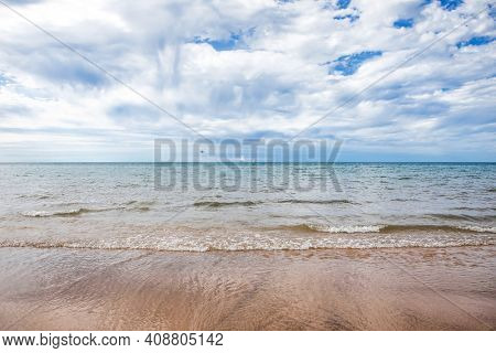 Beach background with sailboats in the distance on Lake Michigan with rain showers over the lake