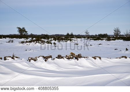 Snowdrift By An Old Dry Stone Wall In A Great Plain Landscape