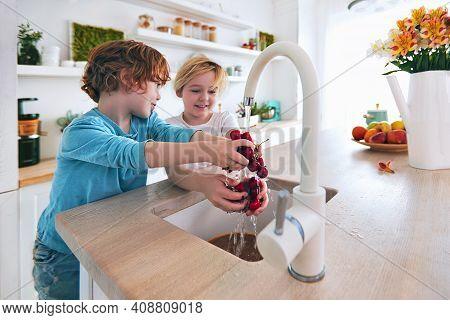 Happy Kids Washing Cherries Under The Tap Water At The Kitchen. Focus On Cherries