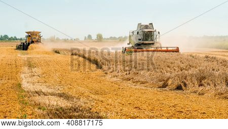 Wheat Harvesting On Field In Summer Season. Two Modern Combine Harvesters With Grain Header, Wide Ch